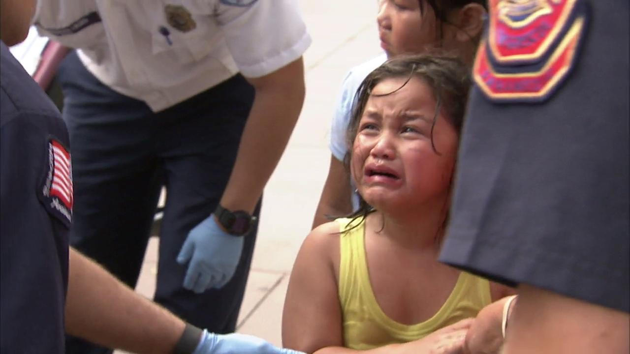 A young girl cries as paramedics treat her after officials said someone sprayed chemicals following a clash between Donald Trump supporters and protesters in Anaheim.