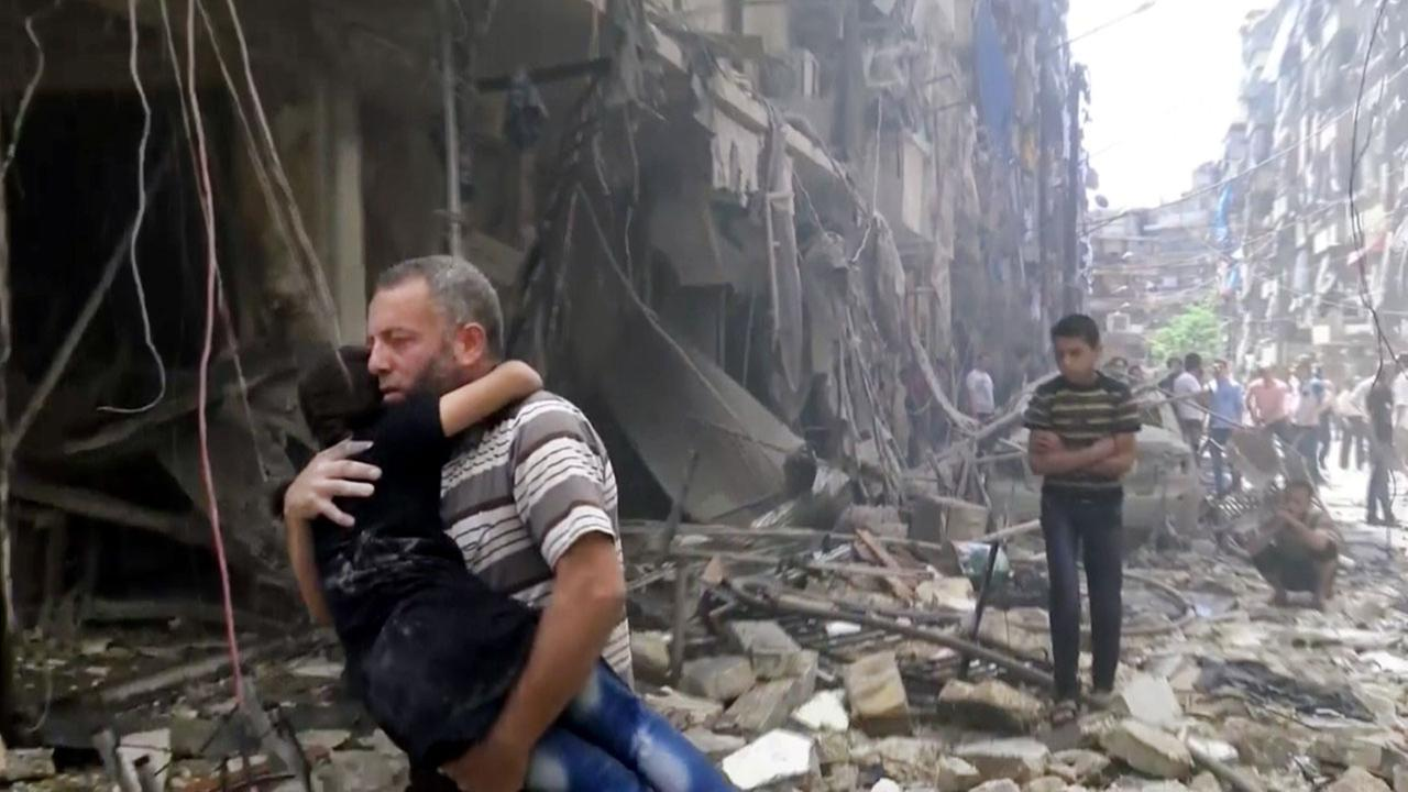 In this image made from video and posted online from Validated UGC, a man carries a child after airstrikes hit Aleppo, Syria, Thursday, April 28, 2016.
