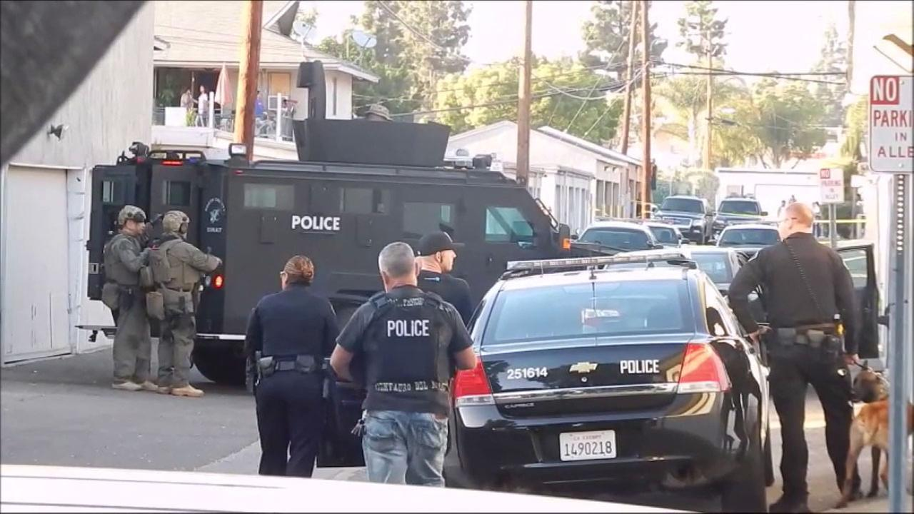 SWAT teams surrounded a Fullerton garage where a possibly armed person has taken someone hostage.