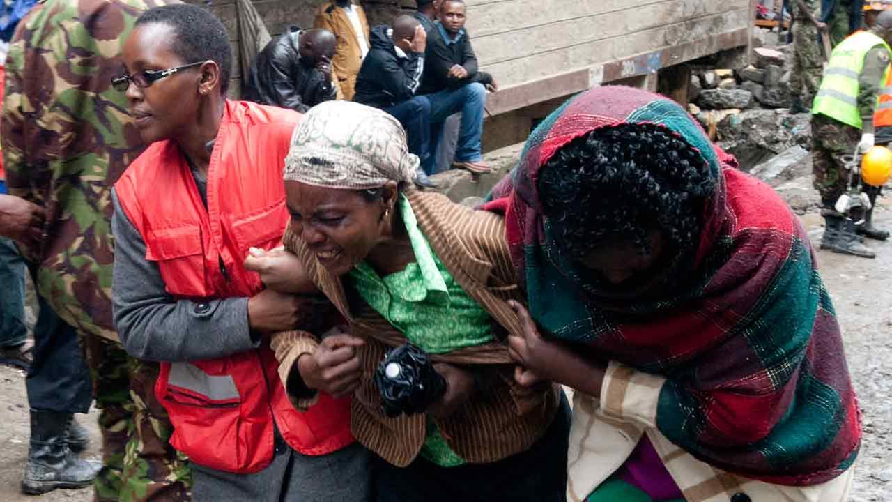 A Kenyan Red Cross personnel and a volunteer console a relative of a victim, at the site of a building collapse in Nairobi, Kenya, Saturday, April 30, 2016.