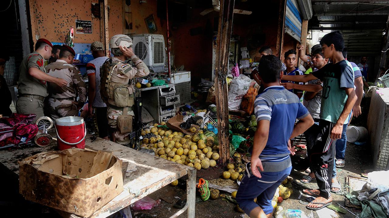 Security forces and citizens inspect the scene after a bomb explosion at an outdoor market in Baghdads northern neighborhood of Shaab, Iraq, Tuesday, May 17, 2016.