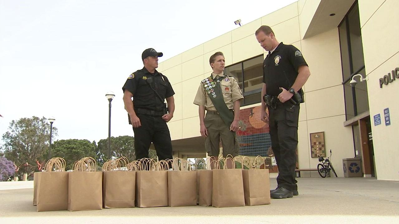 Spencer Nichols works with Huntington Beach police officers to hand out kits hes made for the local homeless community.