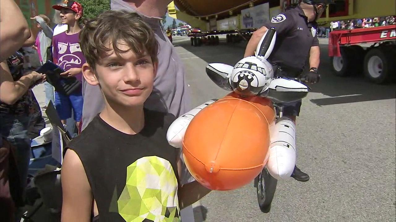 A young science enthusiast holds up an inflatable replica of the completed Endeavour space shuttle.KABC