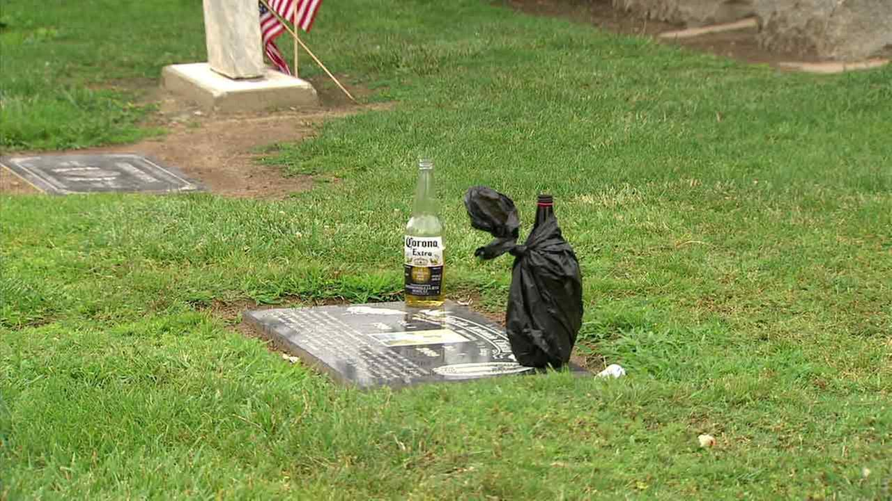Two beer bottles are seen at a grave site where a shooting broke out in Santa Ana, Calif., on Sunday, May 29, 2016.