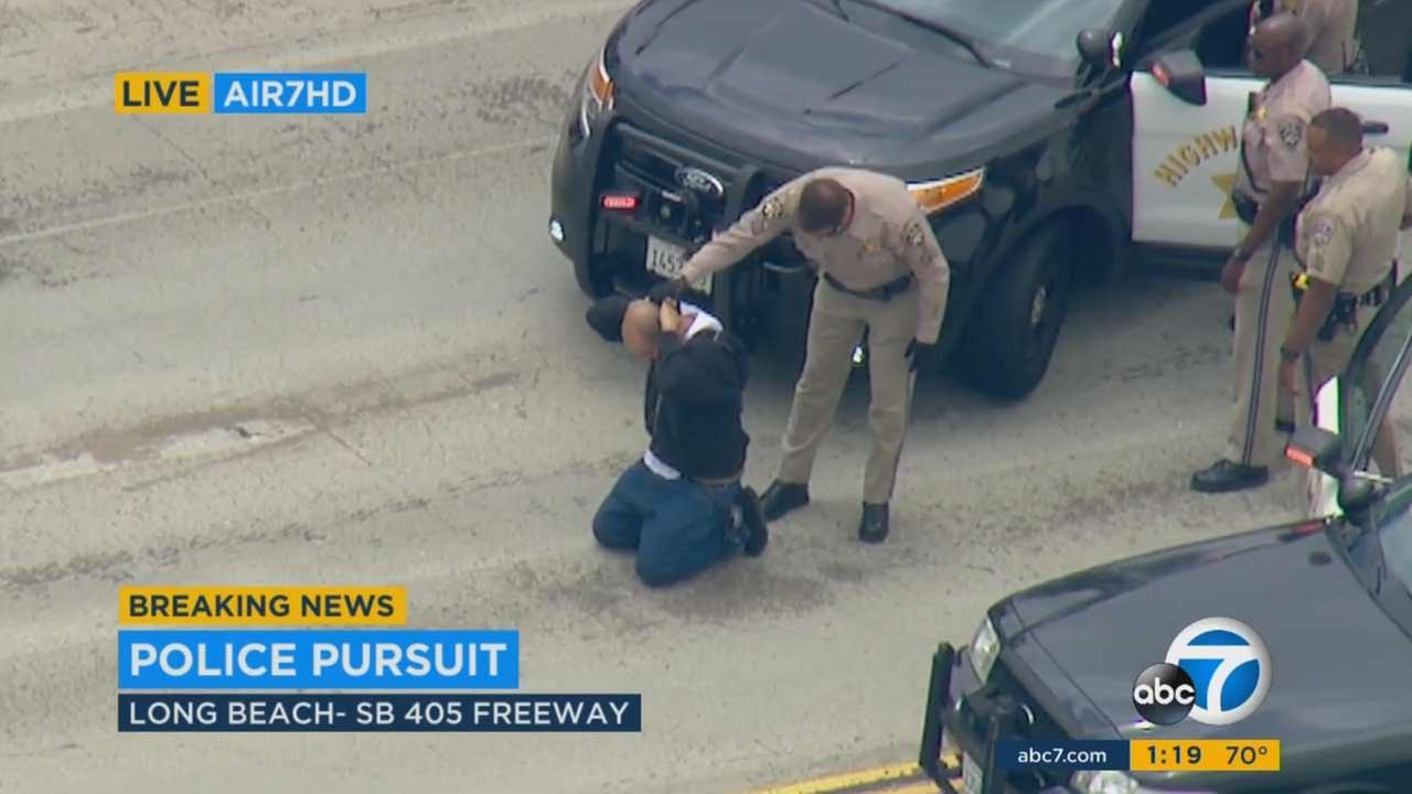 A stolen-car suspect is taken into custody by officers following an hours-long pursuit across Los Angeles County on Monday, May 30, 2016.