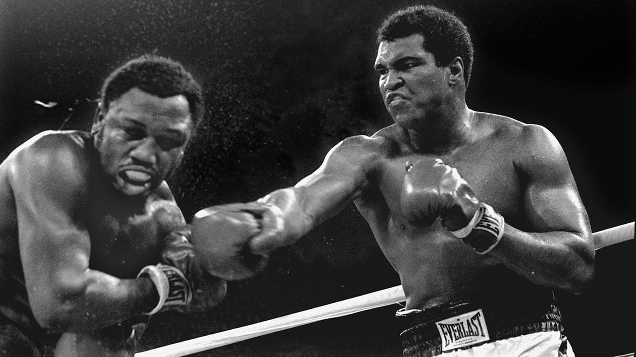 Spray flies from the head of challenger Joe Frazier as heavyweight champion Muhammad Ali connects with a right in Manila, Philippines, October 1, 1975.