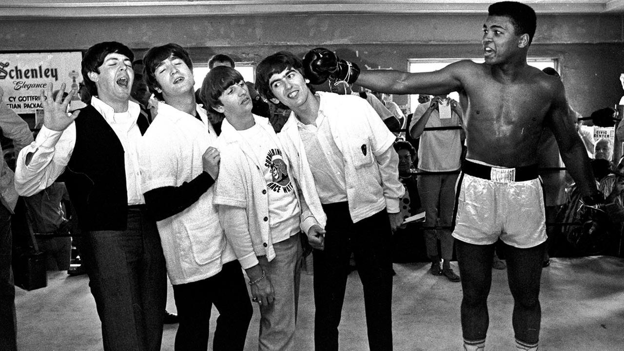 The Beatles, from left, Paul McCartney, John Lennon, Ringo Starr, and George Harrison, take a fake blow from Muhammad Ali in Miami Beach, Fla. on Feb. 18, 1964.