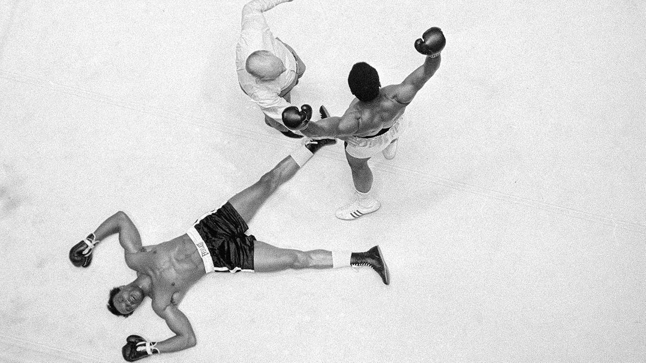Cleveland Williams is spreadeagled on the canvas as referee Harry Kessler sends Muhammad Ali to a neutral corner during their heavyweight bout in Houston on Nov. 14, 1966.