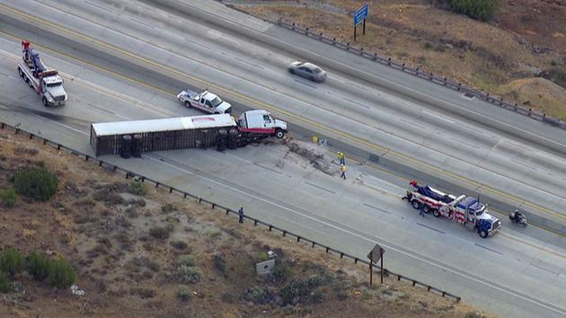 Crews work to remove an overturned semi-truck from blocking all lanes of the southbound 14 Freeway in Agua Dulce on Wednesday, June 8, 2016.