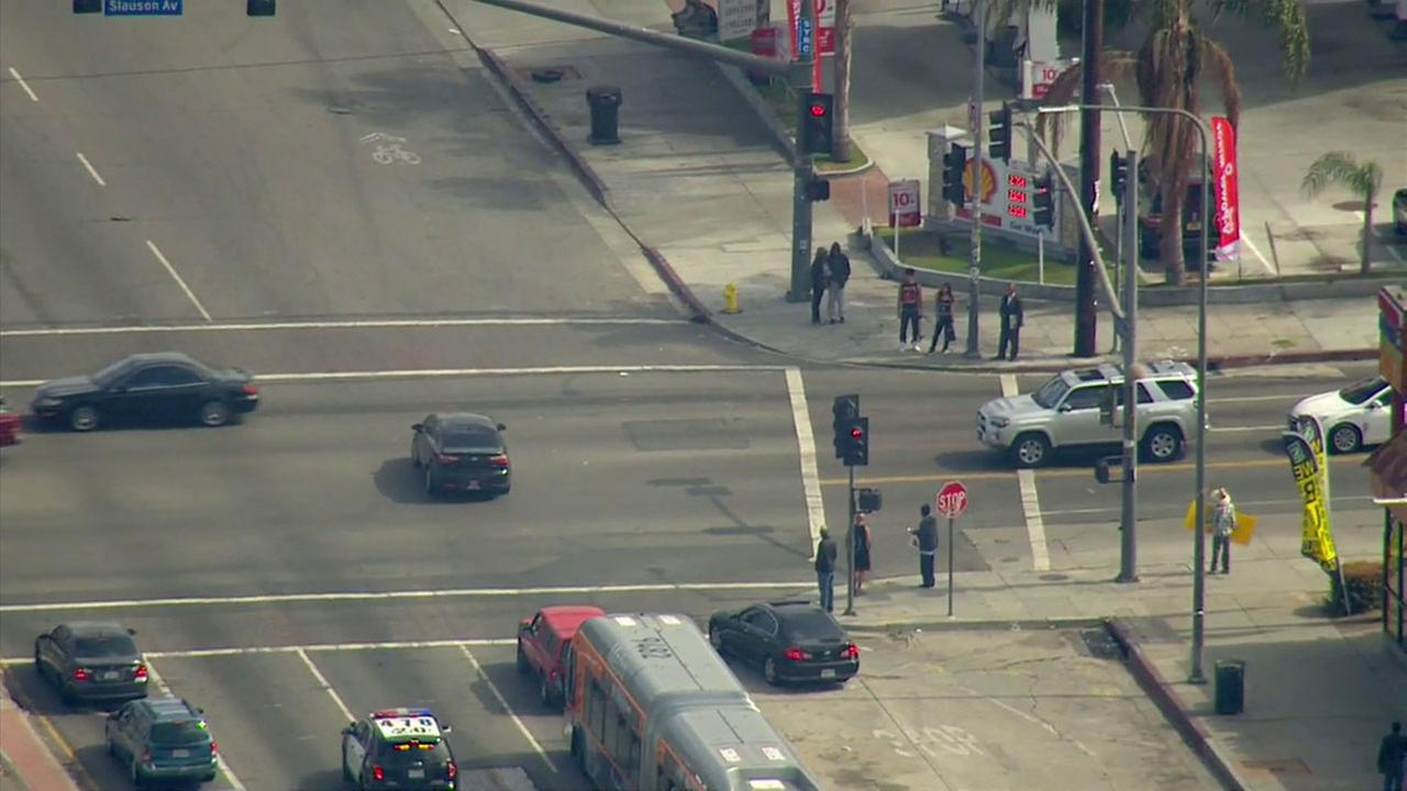 Three suspects in a black car drove through red lights as they fled police in the Mid-City area of Los Angeles on Tuesday, June 14, 2016.
