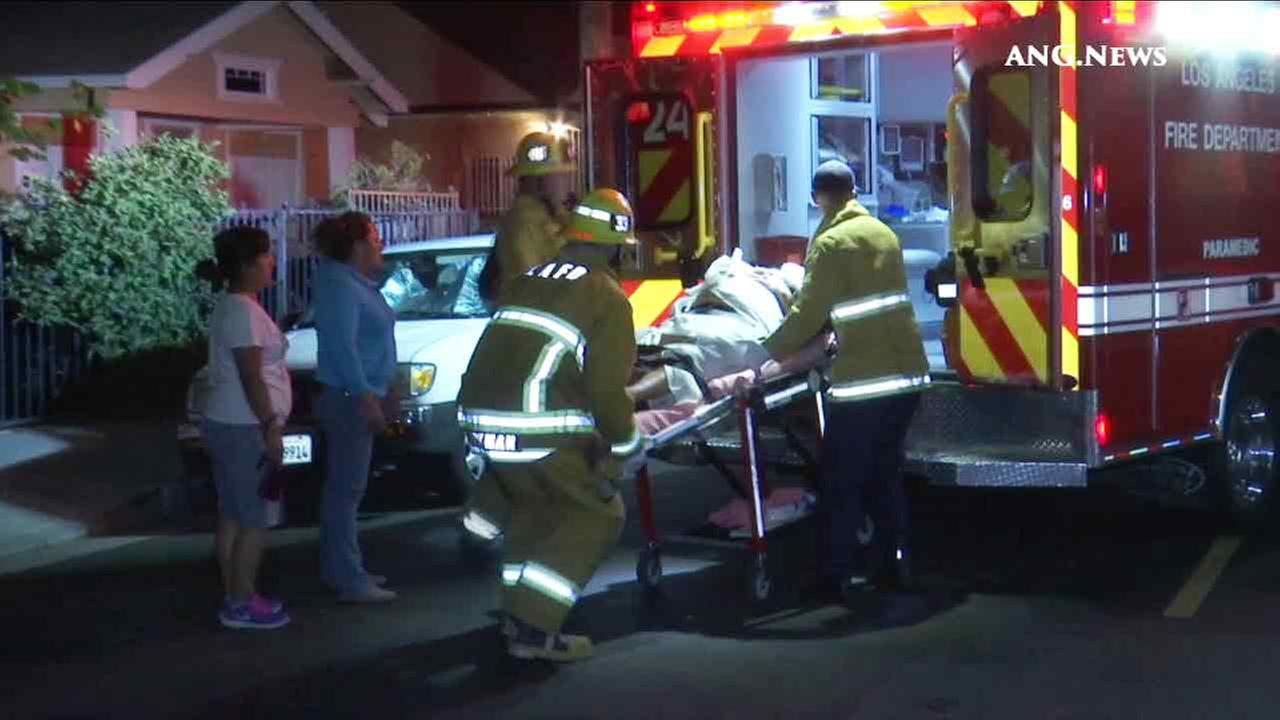 Los Angeles City firefighters help transport a pregnant woman struck in a South Los Angeles hit-and-run crash on Saturday, June 18, 2016.