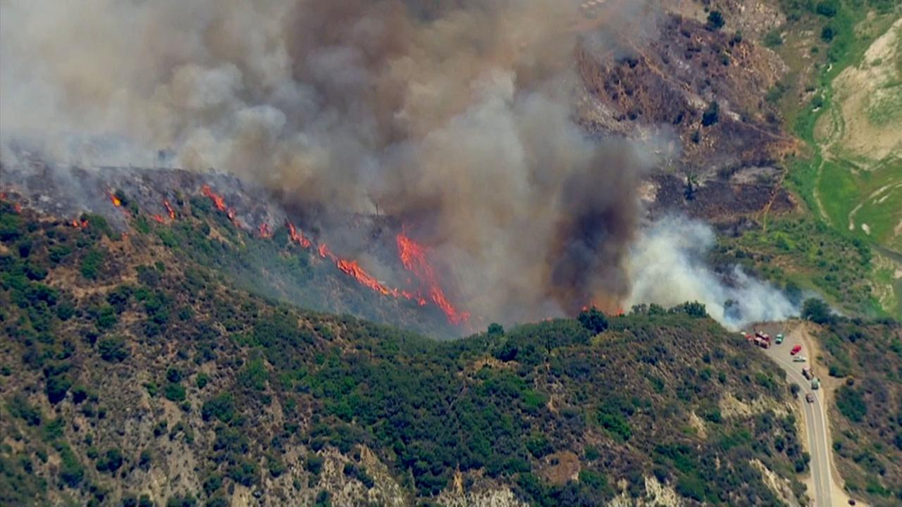 Smoke and flames burn through the Angeles National Forest above Azusa, dubbed the Reservoir Fire, on Monday, June 20, 2016.