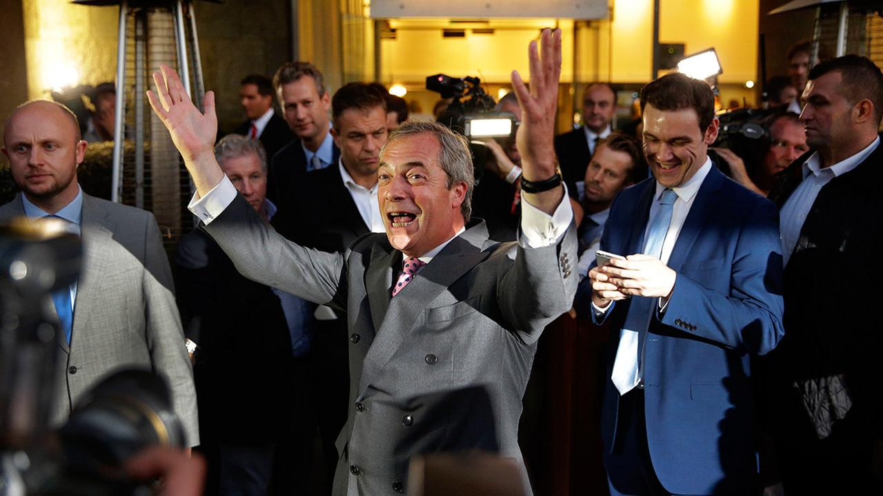 Nigel Farage, the leader of the UK Independence Party, celebrates and poses for photographers as he leaves a Leave.EU organization party in London on Friday, June 24, 2016.