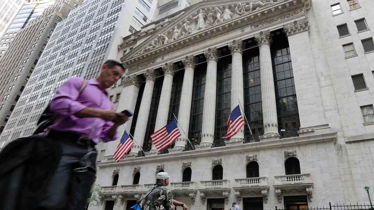 A man passes the New York Stock Exchange, Friday, June 24, 2016.