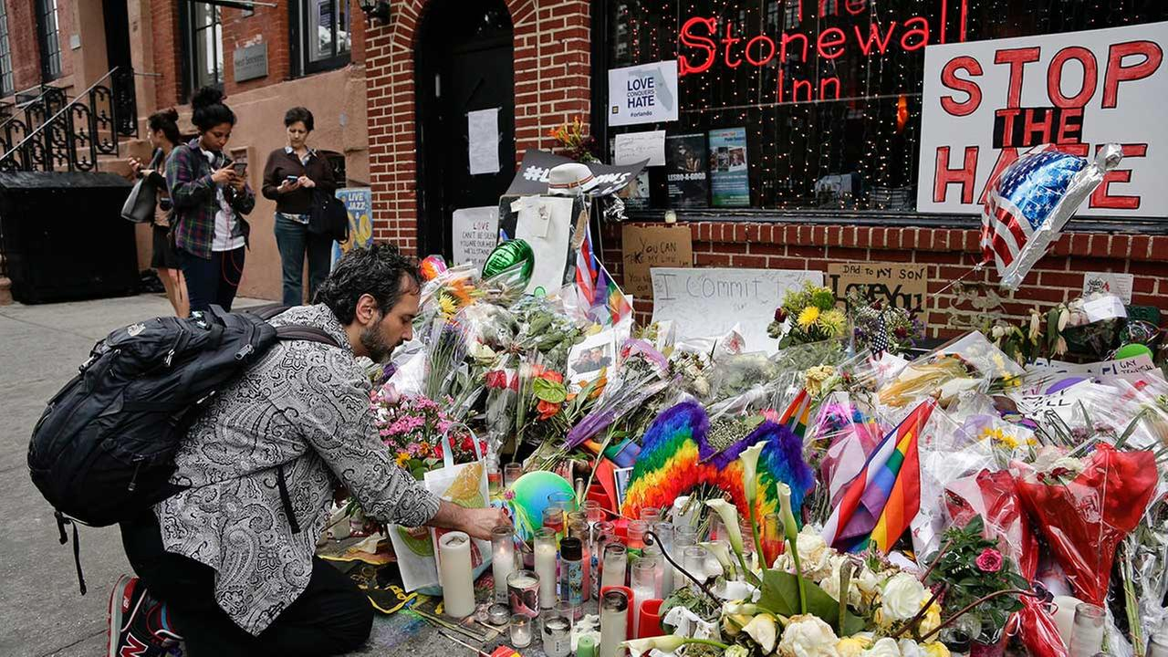In this June 16, 2016 file photo, a man lights candles on a memorial outside the Stonewall Inn for victims of the Orlando Shooting, in New York.