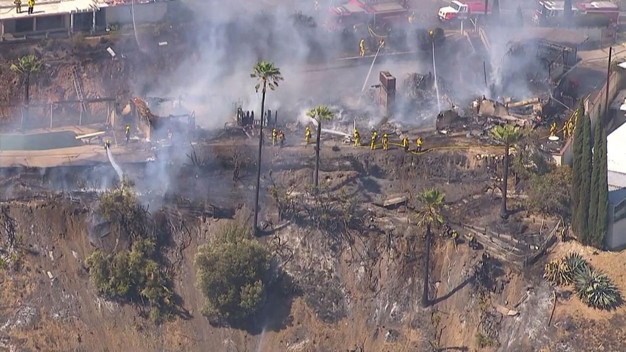 Firefighters douse the smoking ruins of homes in San Bernardino destroyed by a brush fire.