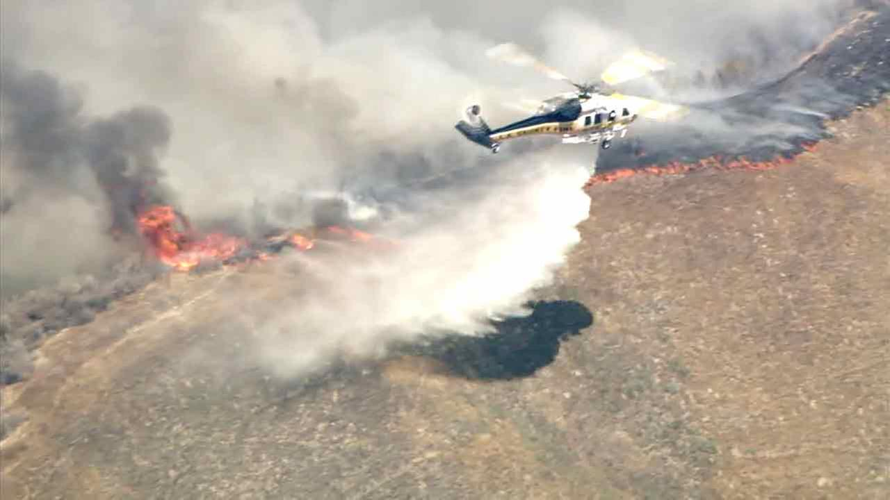 Fire crews are seen dropping water onto the Sage Fire from the air on Saturday, July 9, 2016.