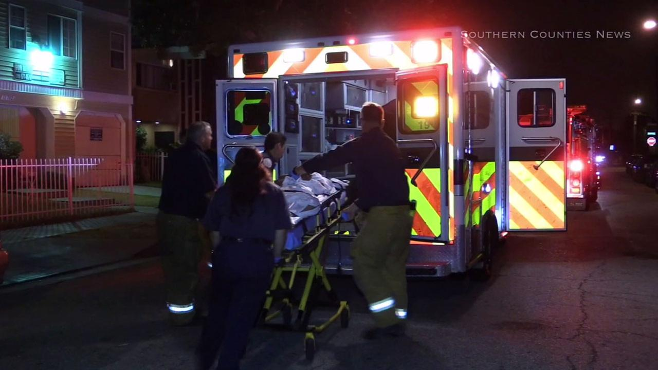 EMTs rush a woman suffering from gunshot wounds into an ambulance after she was found shot in Hawthorne on Wednesday, July 13, 2016.