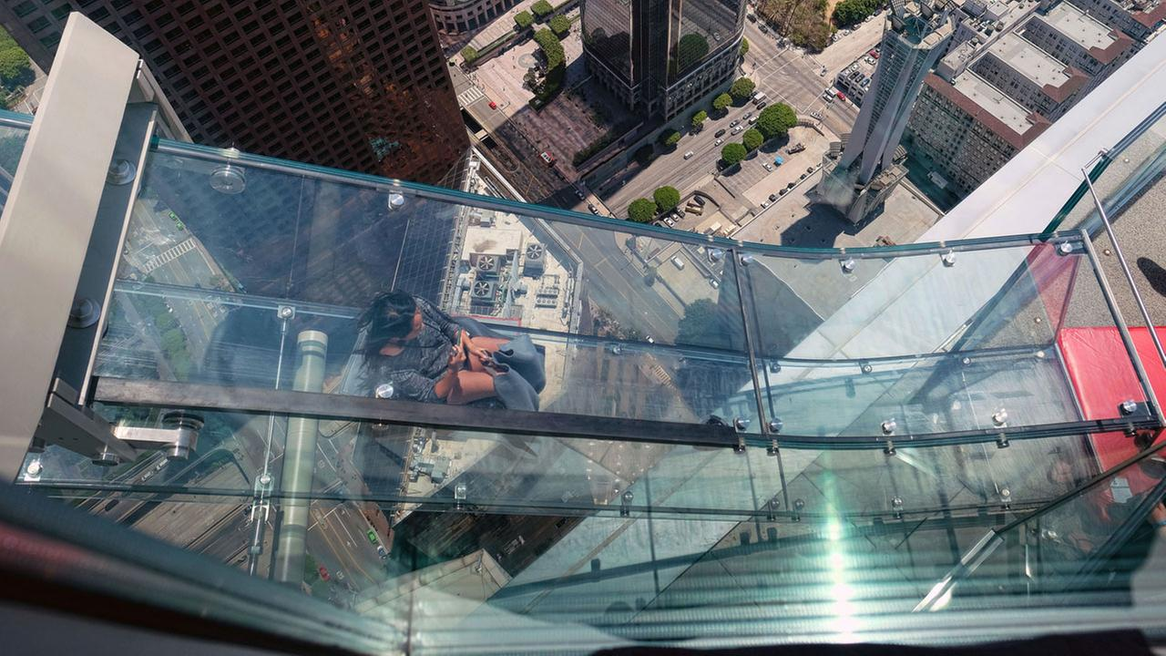 A member of the media rides down a glass slide during a media preview at the U.S. Bank Tower building in downtown Los Angeles on Thursday, June 23, 2016.