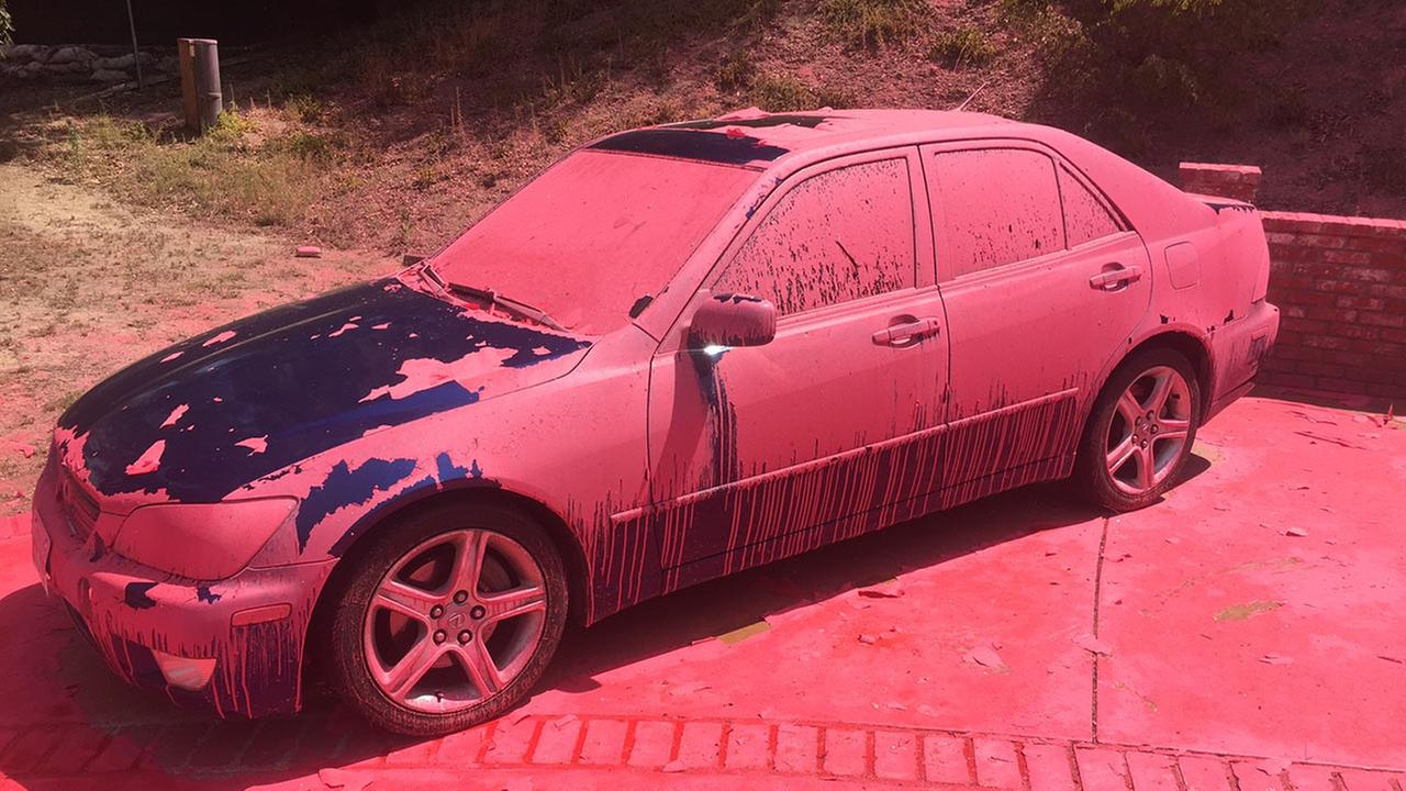 A car covered in aerially-applied fire retardant remains parked in Ruthspring Dr., in Santa Clarita, Calif., on Sunday, July 24, 2016.AP Photo/Matt Hartman