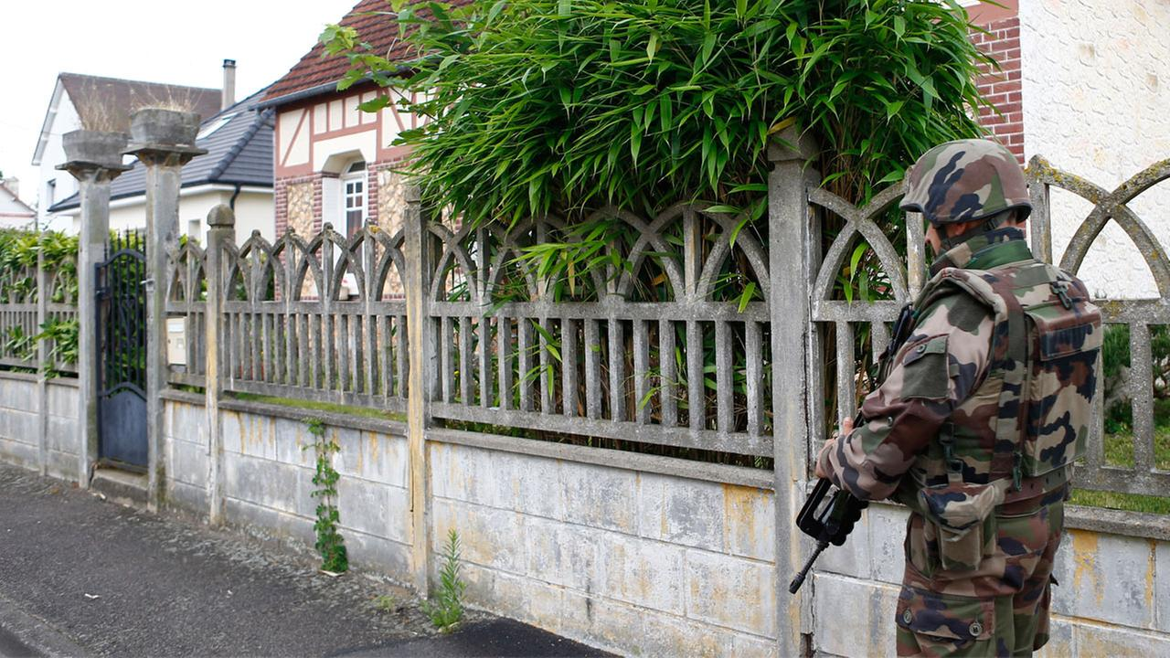 A French soldiers stands guard as he prevents the access to the scene of an attack in Saint-Etienne-du-Rouvray, Normandy, France, Tuesday, July 26, 2016.