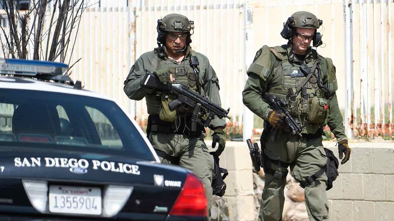 San Diego Police SWAT officers walk down the street after entering a house with a possible suspect inside Friday, July 29, 2016, in San Diego.