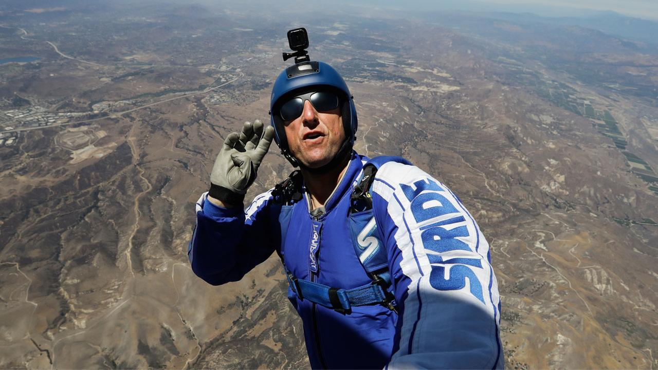 In this Monday, July 25, 2016 photo, skydiver Luke Aikins signals to pilot Aaron Fitzgerald as he prepares to jump from a helicopter in Simi Valley, Calif.