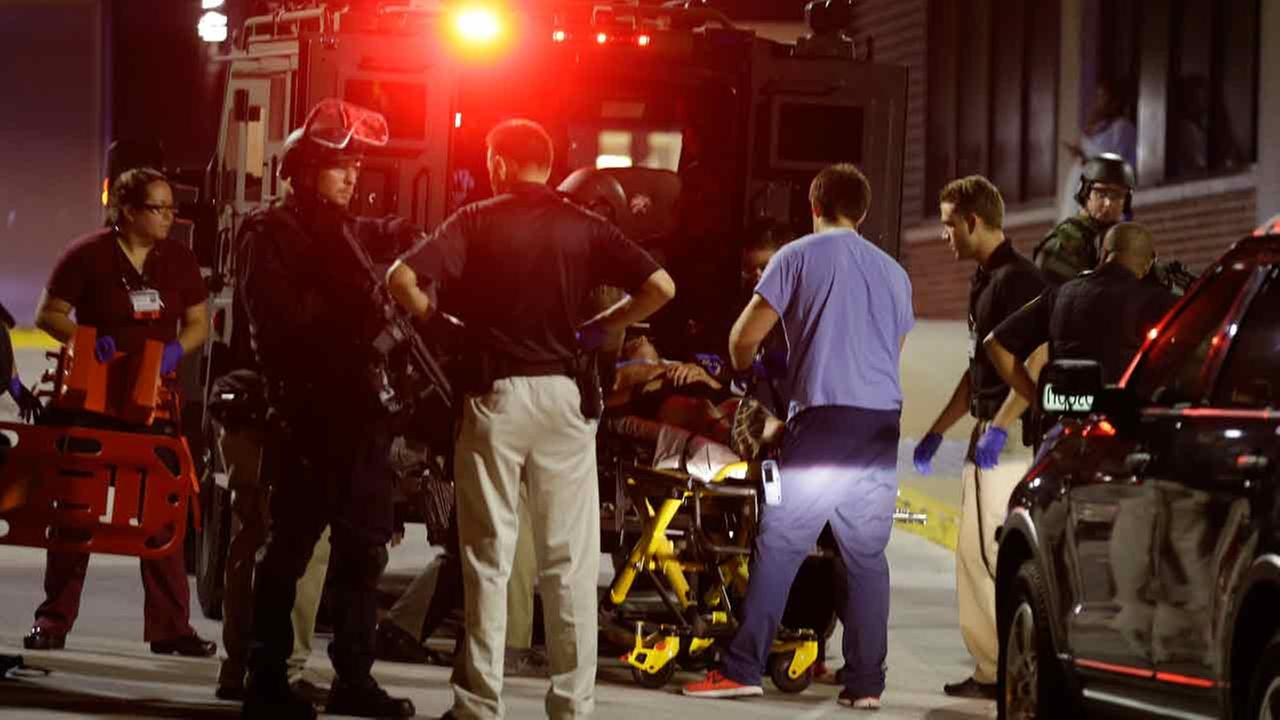 Armed police transport a man to a hospital after getting injured during unrest in Milwaukee, Sunday, Aug. 14, 2016.