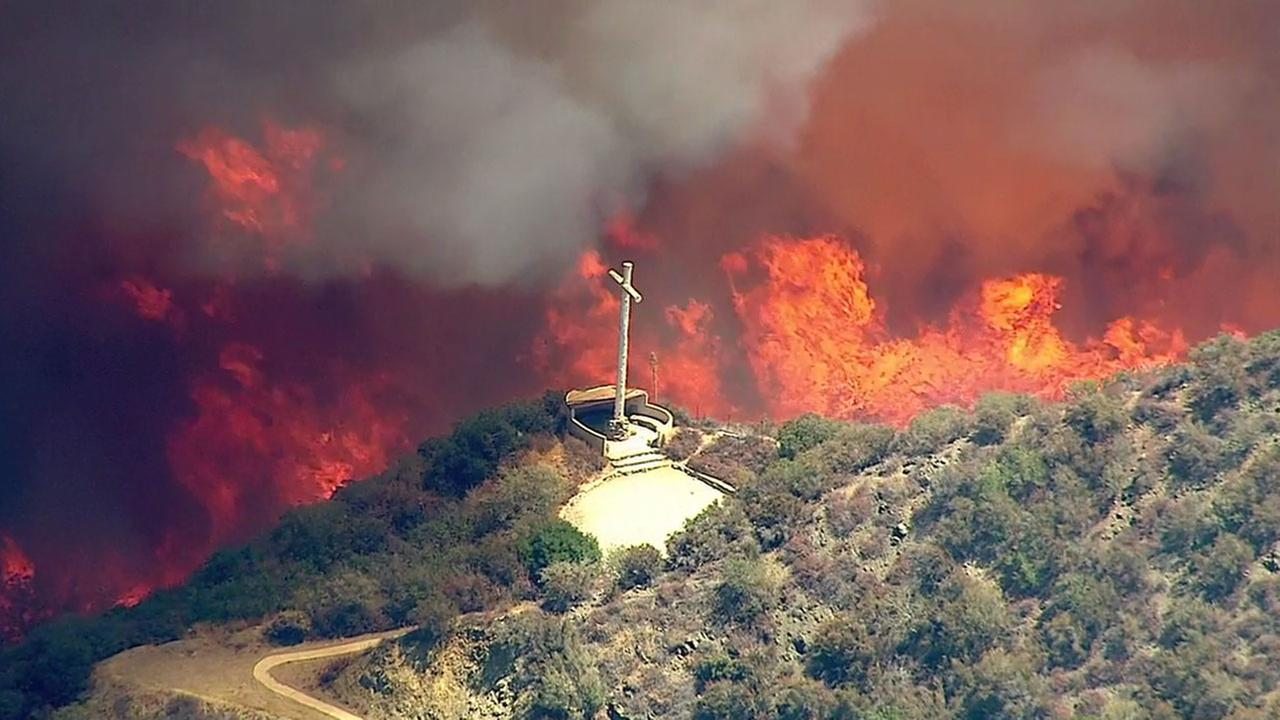 Flames burn close to a cross on a hill above Devore on Tuesday, Aug. 16, 2016.