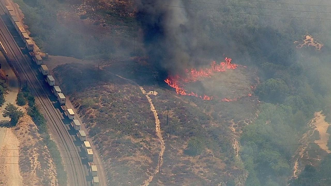 A small patch of brush burned near a railroad and the 15 Freeway near Devore before exploding into a large brush fire on Tuesday, Aug. 16, 2016.
