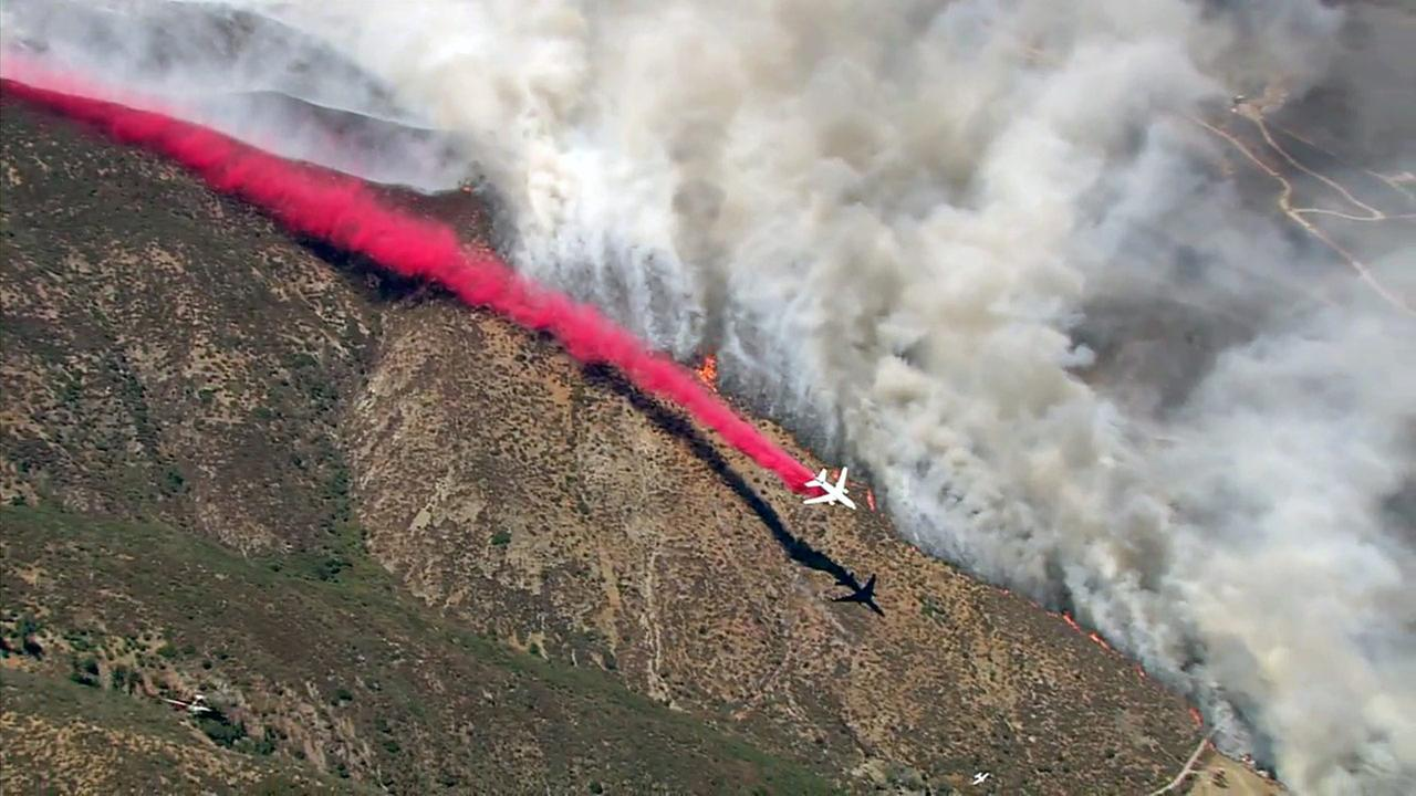 A plane drops fire retardant while battling the Blue Cut Fire in the San Bernardino National Forest on Tuesday, Aug. 16, 2016.