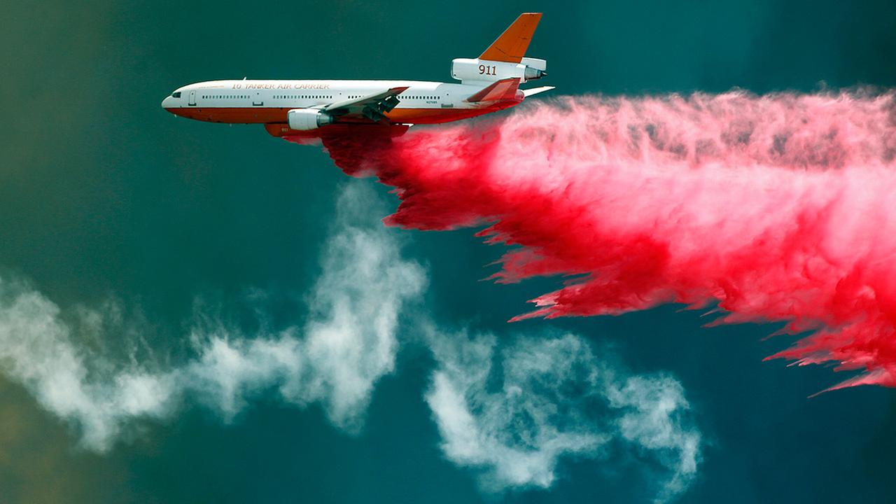 A DC-10 air tanker delivers flame retardant to the Blue Cut fire in Wrightwood, Calif., Wednesday, Aug. 17, 2016.