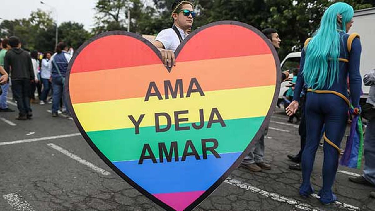 A man carries a heart that reads in Spanish Love and let love at a gay pride parade in Lima, Peru on June 28, 2014.