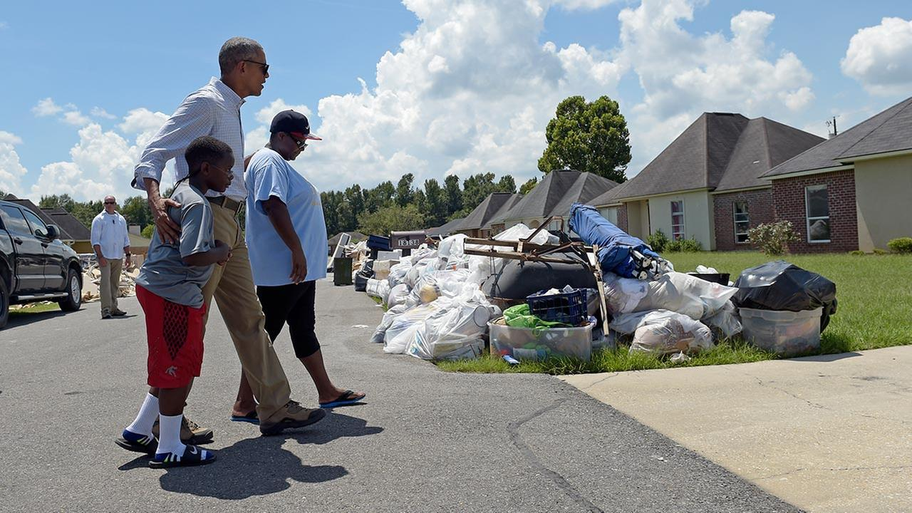 President Barack Obama walks with a family to tour their flood-damaged home in the Castle Place neighborhood of Baton Rouge, La., Tuesday, Aug. 23, 2016.