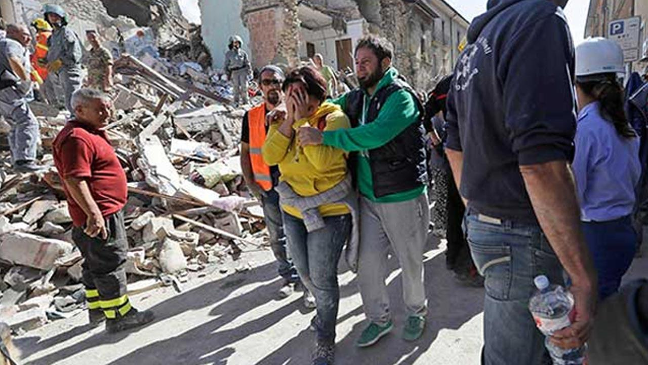 A woman is comforted as she walks through rubble after an earthquake, in Amatrice, central Italy, Wednesday, Aug. 24, 2016.