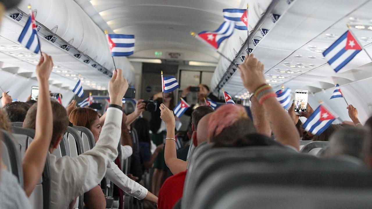 Shortly after take-off from Fort Lauderdale airport customers are seen waving Cuban flags while onboard JetBlues inaugural commercial flight to Cuba on Wednesday, Aug. 31, 2016.