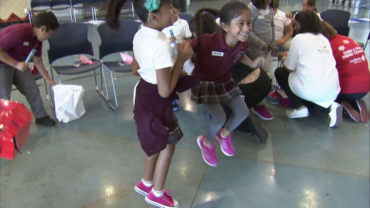 Students jump for joy at Vaughn Next Century Learning Center in Pacoima after receiving free sneakers and other goodies on the first day of school.