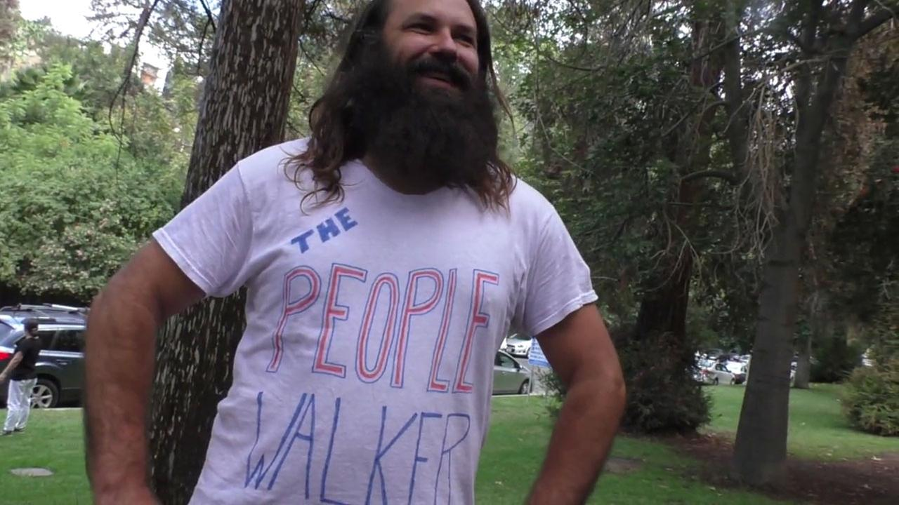 Chuck McCarthy shows off his people walker shirt, which he wears while walking with people as a second job.