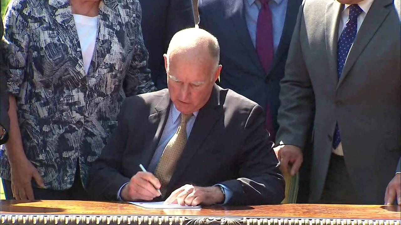 Gov. Jerry Brown signs legislation that targets the reduction of greenhouse gas emissions in California in Los Angeles on Thursday, Sept. 8, 2016.