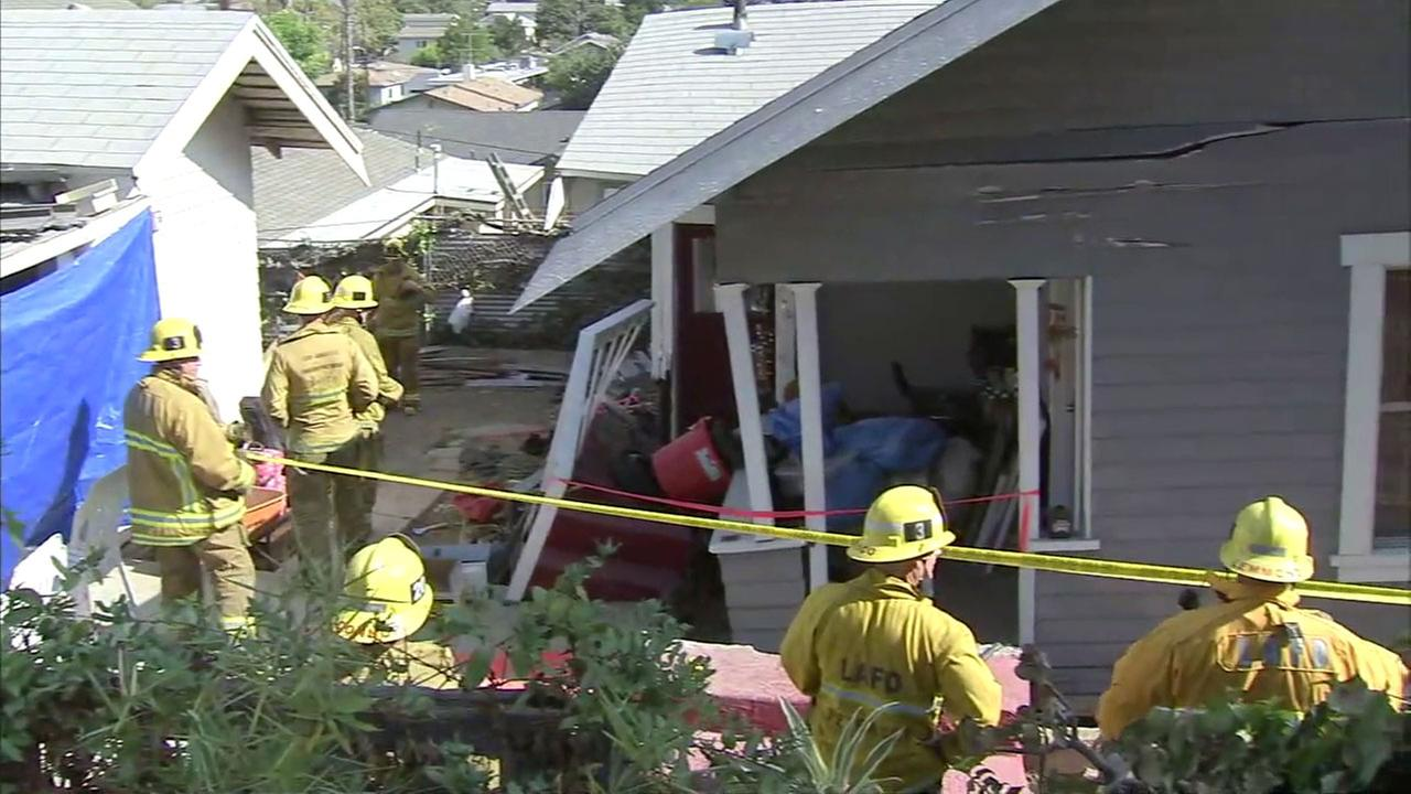 Firefighters assess the damage of a small home after its foundation gave way, causing it to collapse in Echo Park on Wednesday, Sept. 14, 2016.
