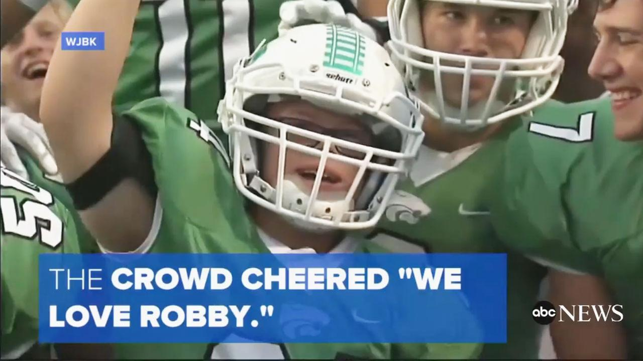Robby Heil, a senior at Novi High School with Down syndrome, cheers along with his teammates after scoring a touchdown.