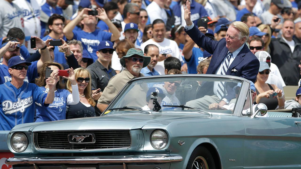 Vin Scully acknowledges the fans as he arrives to throw the ceremonial first pitch before a baseball game on Friday, April 4, 2014, in Los Angeles.AP Photo/Jae C. Hong