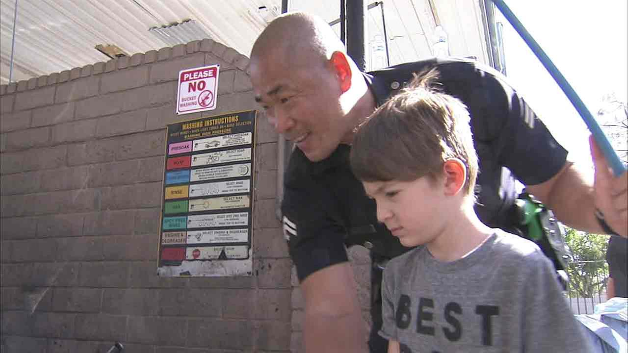 A Topanga Division police officer and Sebastian wash a car as part of the 6-year-olds fundraiser, held to help get the boy an autism service dog.