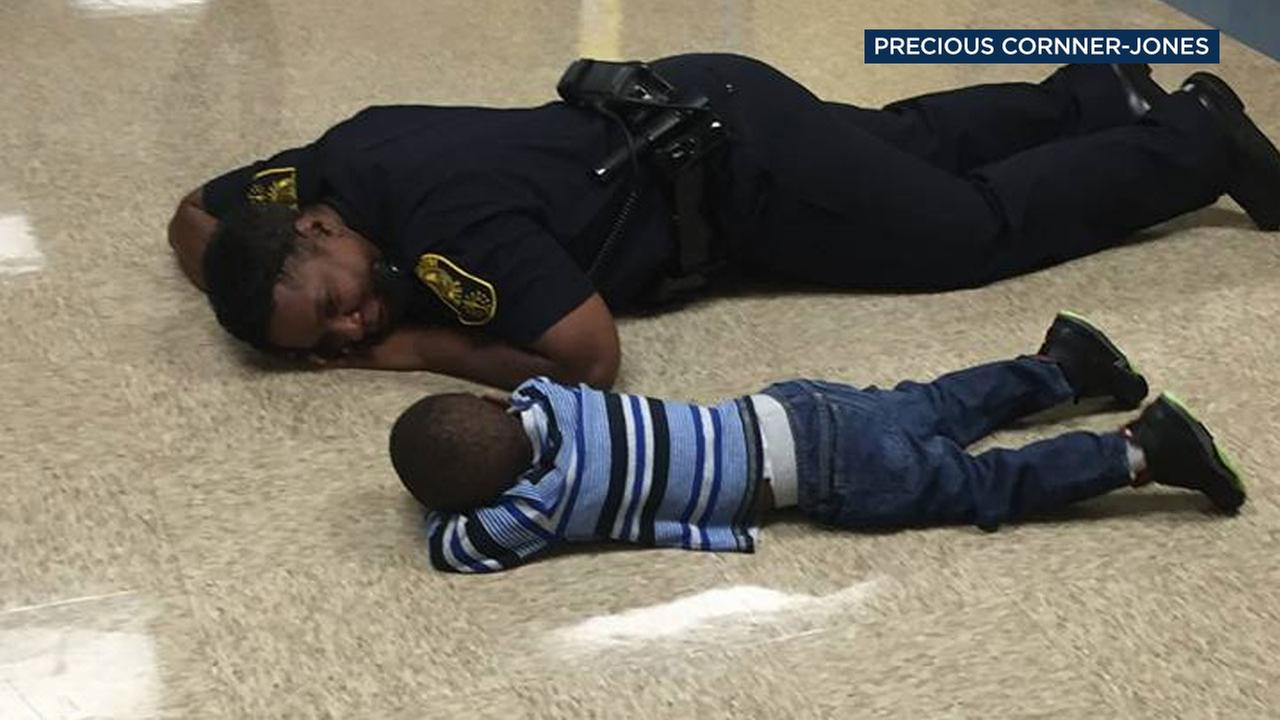 Indianapolis State Officer Precious Cornner-Jones is seen on the ground next to a 4-year-old boy who was having a bad day.