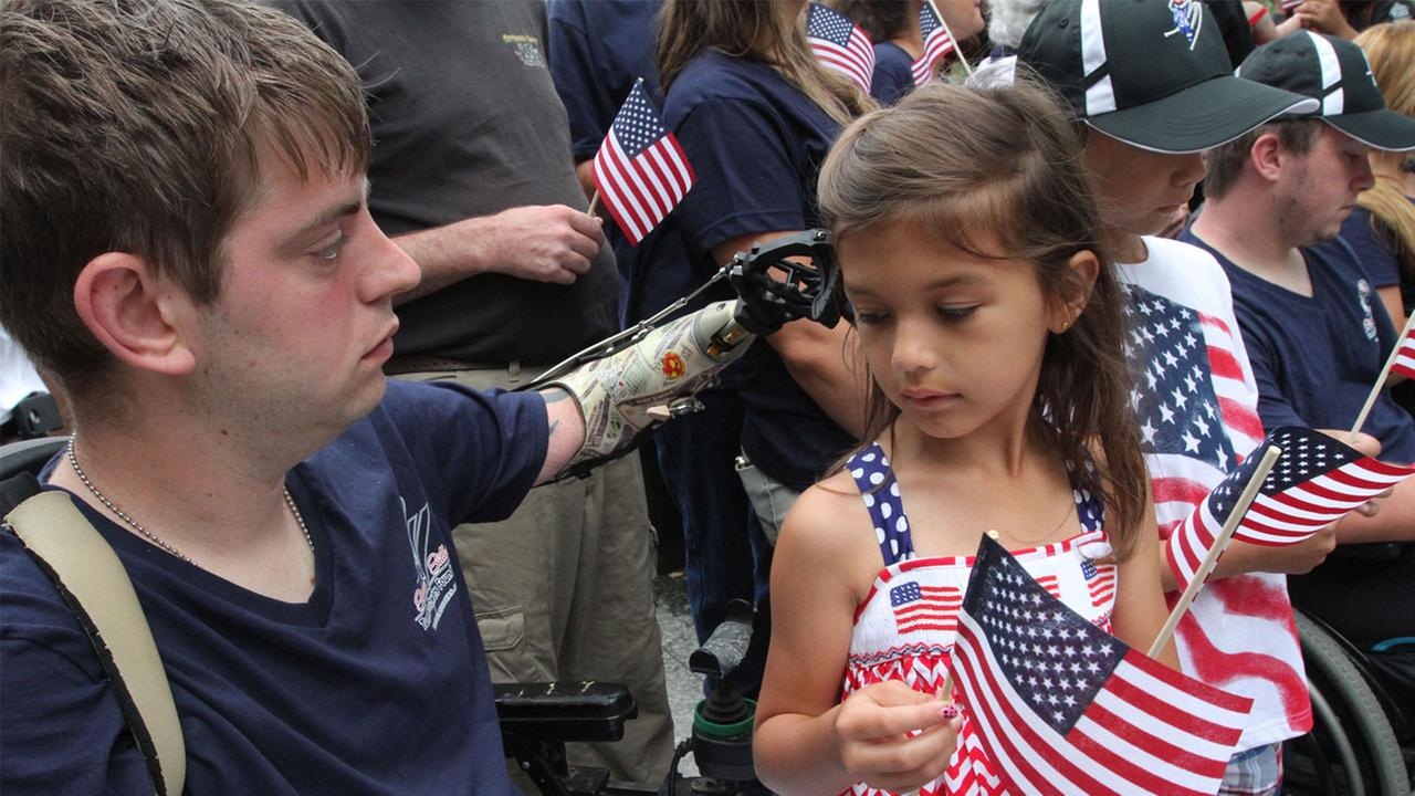 Retired Marine Sgt. John Peck, of Fredricksburg, Va., left, and Sophia Elwood, 7, the daughter of Pecks fiancee, share a moment at the 9/11 Memorial in New York, Friday, July 4, 2014.