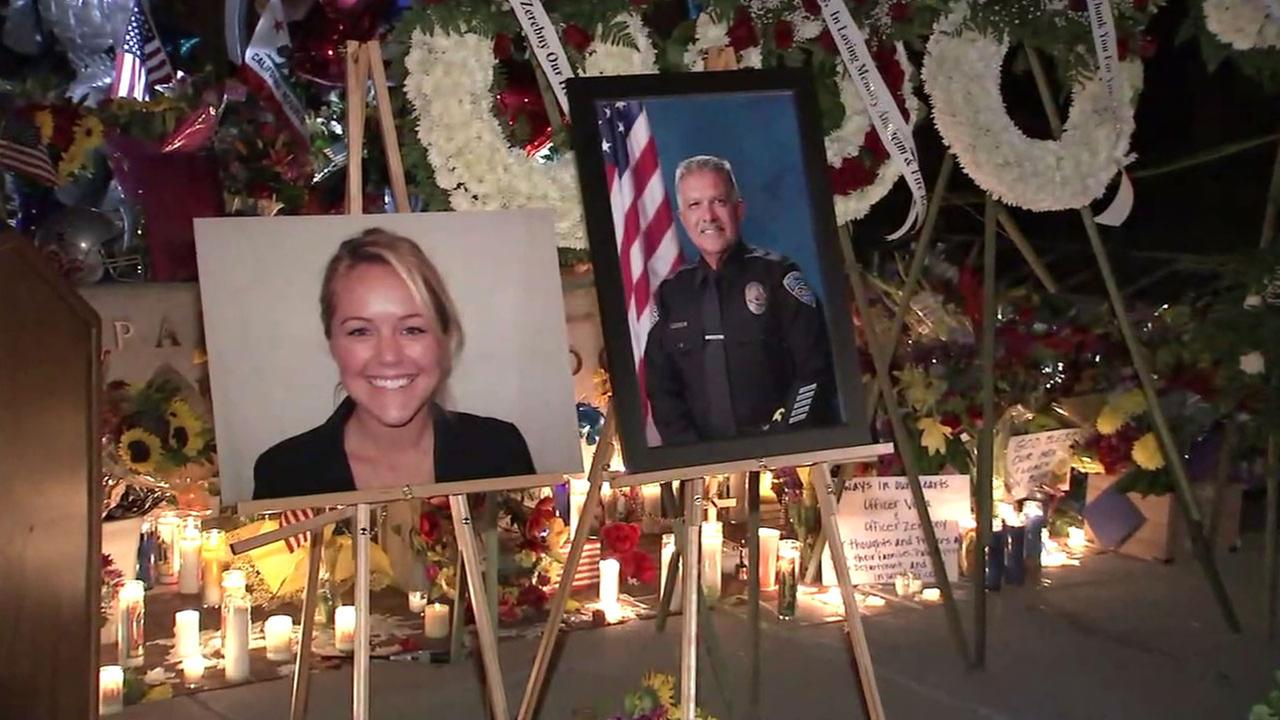 The photos of slain officers Jose Vega, 63, and Lesley Zerebny, 27, are shown in a growing memorial outside of the Palm Springs Police Department on Sunday, Oct. 9, 2016.