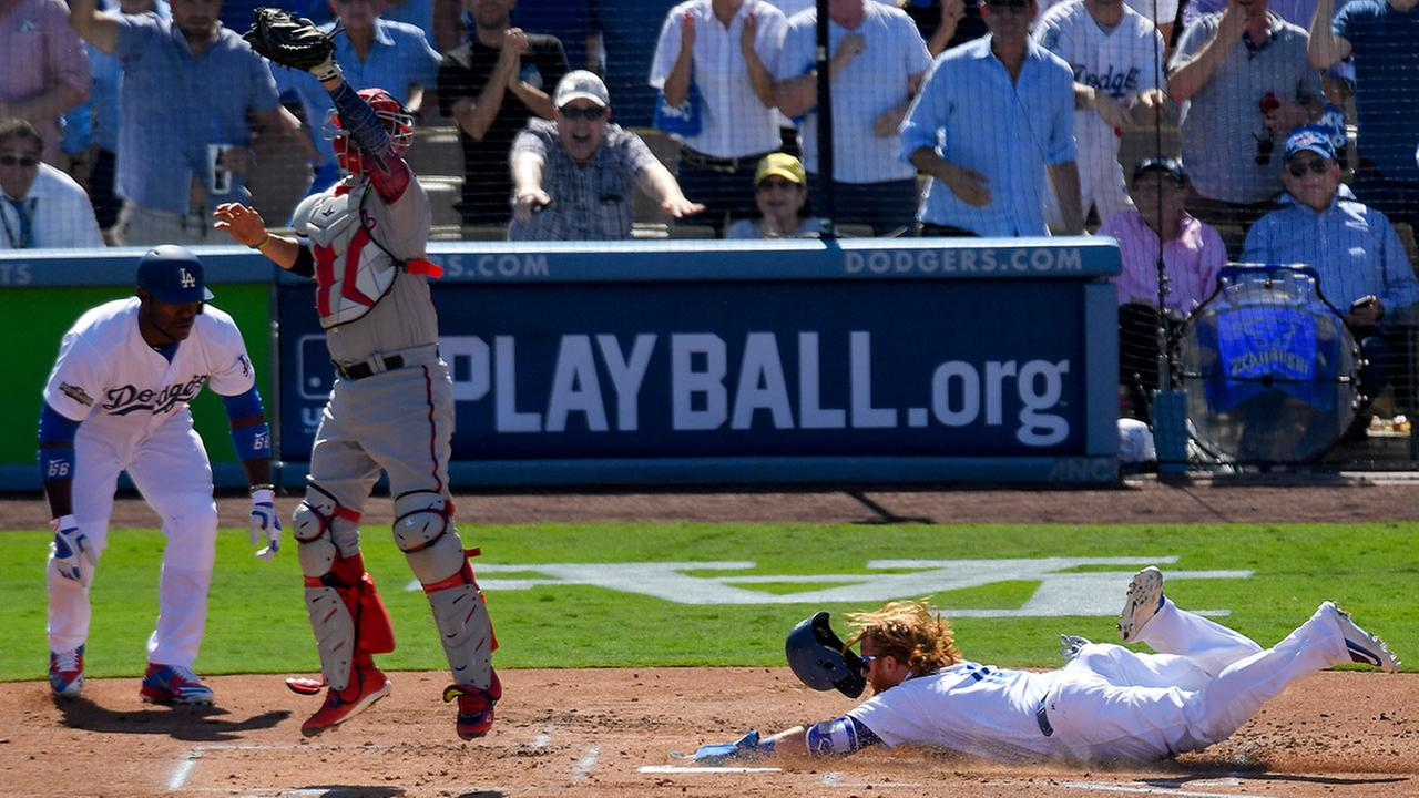 The Dodgers Justin Turner scores past Washington Nationals catcher Jose Lobaton on a double by Corey Seager during Game 3 of the NLDS in Los Angeles on Monday, Oct. 10, 2016.