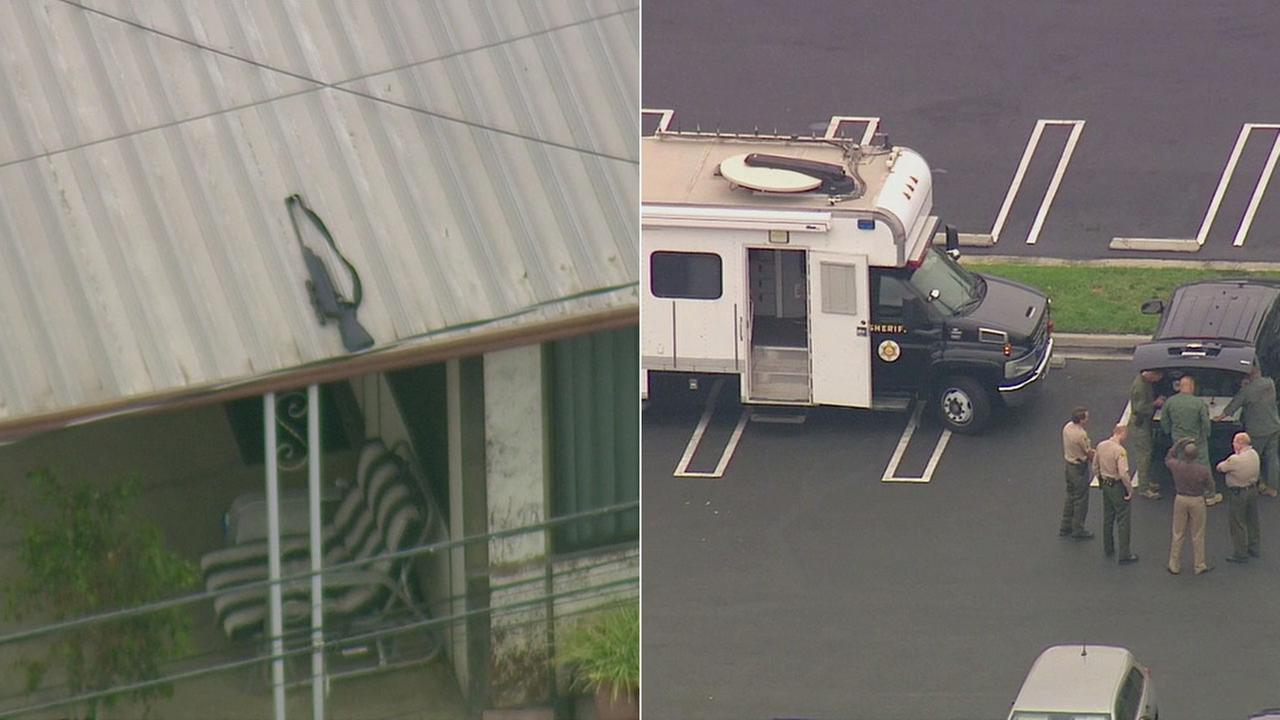 Los Angeles County sheriffs investigators are seen in Lakewood amid a barricaded suspect situation. At one point, what appeared to be a rifle was seen on the roof of the house in question.