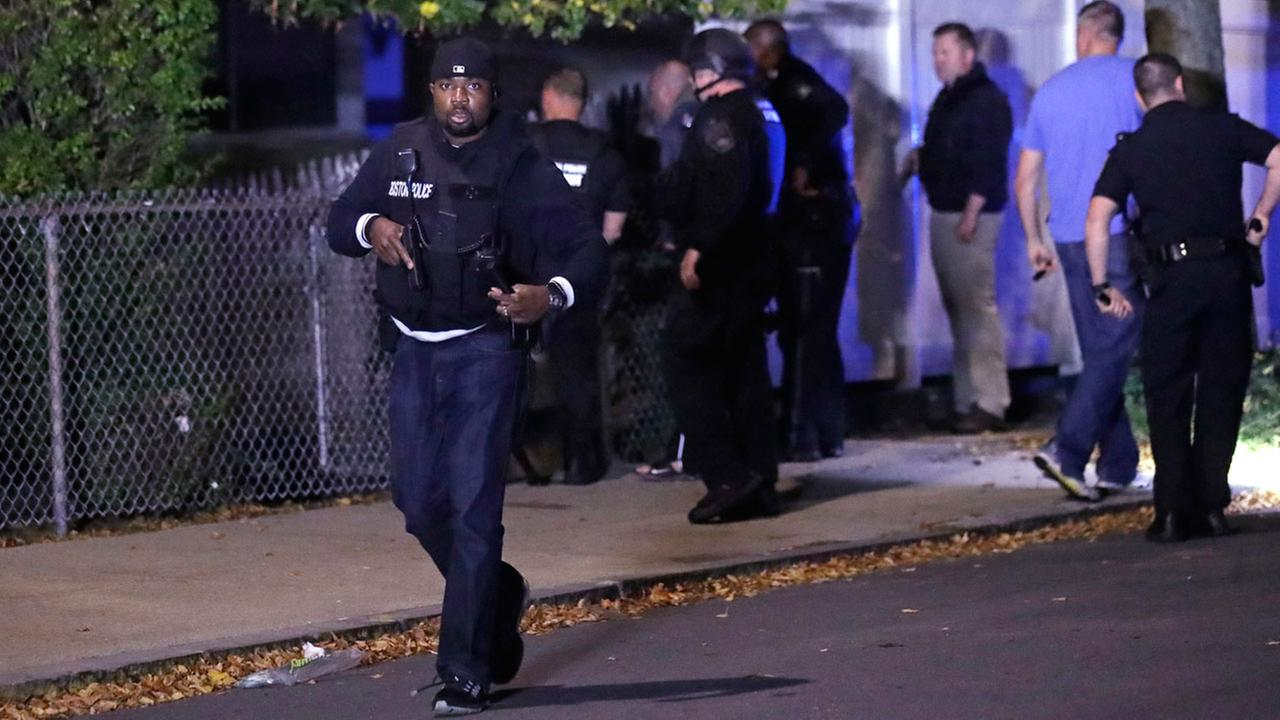 Police search for a suspect after a shooting in the East Boston neighborhood of Boston, Wednesday, Oct. 12, 2016.