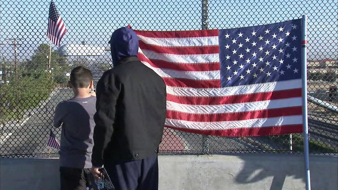 A man and a boy watch a procession in honor of slain L.A. County sheriffs Sgt. Steve Owen in Lancaster on Thursday, Oct. 13, 2016.KABC